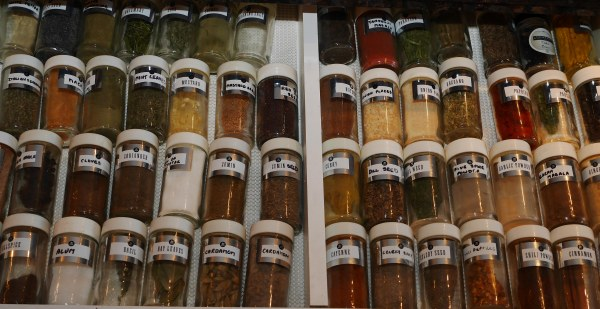 drawer filled with organized, alphabetized spice jars with white lids